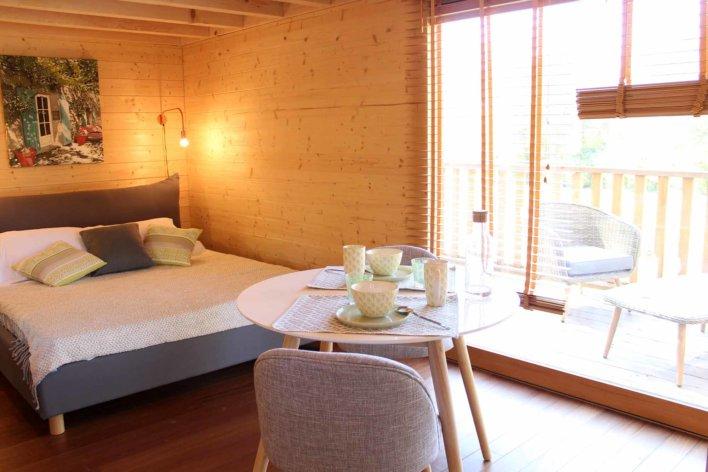 Intérieur d'une cabane en bois avec lit double et table ronde dressée pour un petit-déjeuner