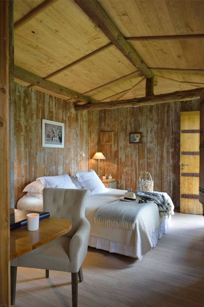 Chambre toute en bois avec lit double et fauteuil capitonné gris