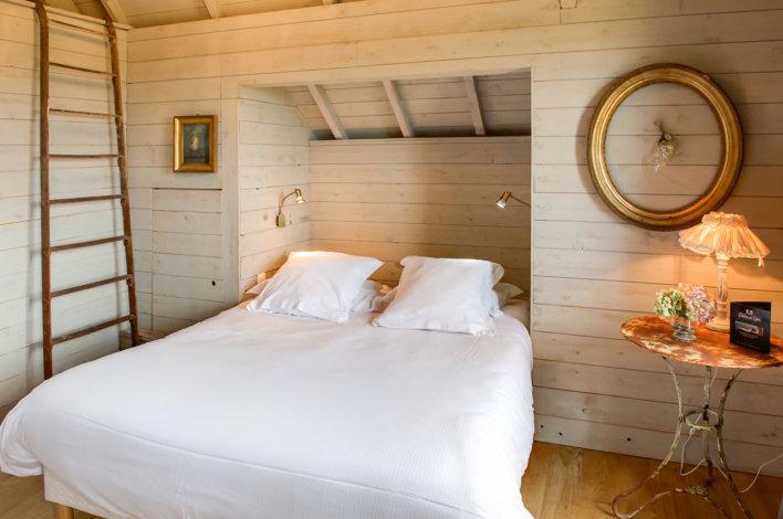 Chambre lit double recouverte de bois, déco campagne chic