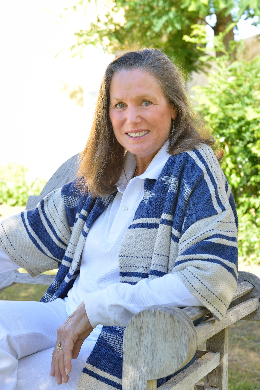 Femme assise sur une chaise de jardin, elle porte un chale rayé bleu et blanc et dessous un chemisier blanc