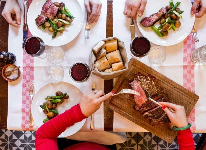 Table de bistrot avec une femme qui sert un morceau de viande