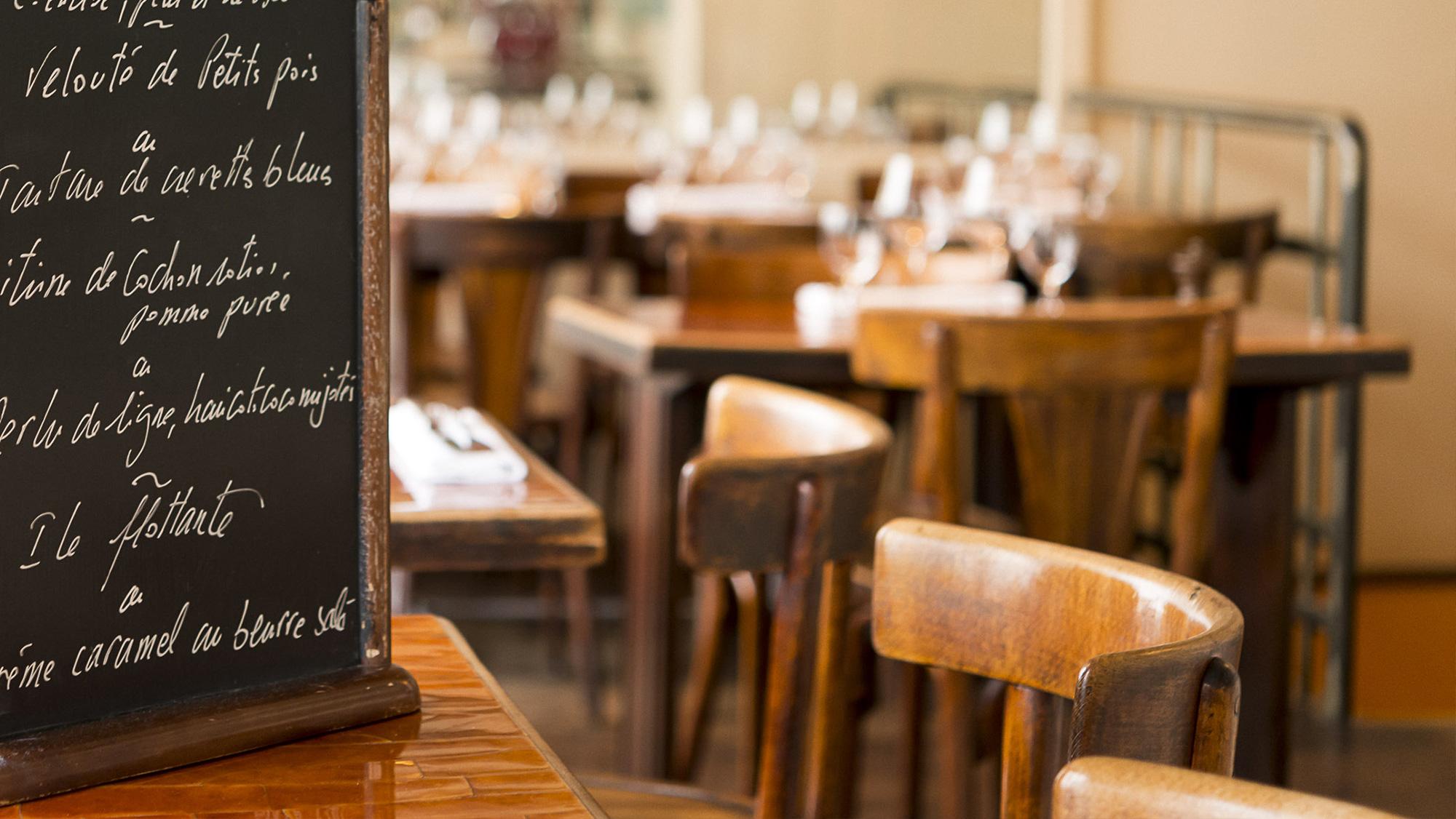 Close-up sur une ardoise de menu sur une table avec mobilier en bois typique bistrot