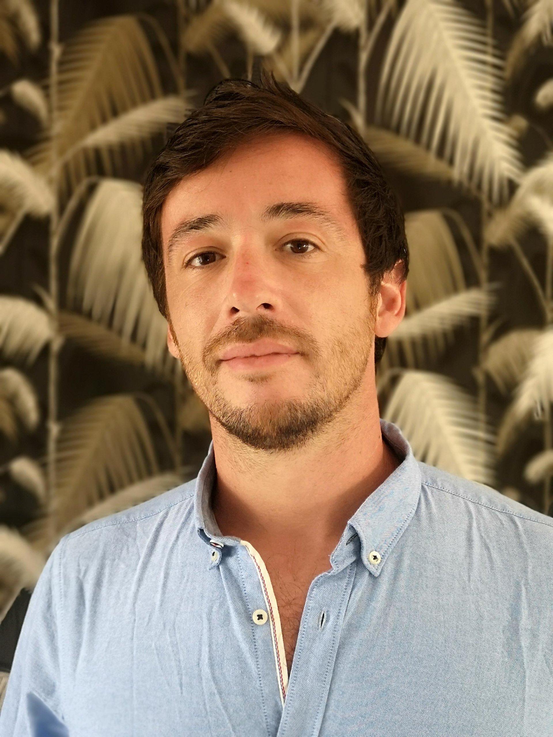 Portrait d'un homme en chemise bleu, arrière plan papier peint noir avec motifs feuilles exotiques dorées