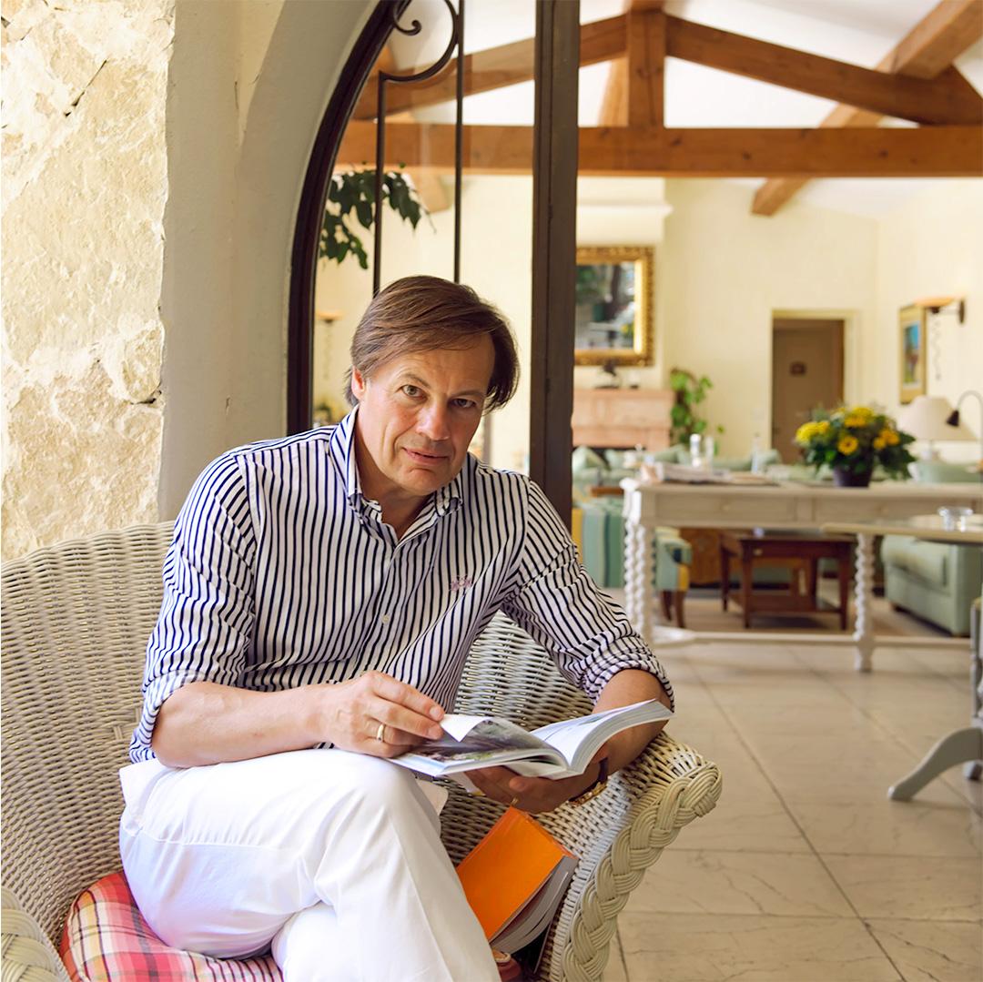 Photo d'un homme assis dans un fauteuil tressé, jambe croisée avec pantalon blanc et chemise à rayure verticale bleu et blanche, il tient un livre dans ses mains
