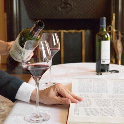 Vin servit au verre sur une table nappée blanche, un homme pose sa main droite sur un livre ouvert