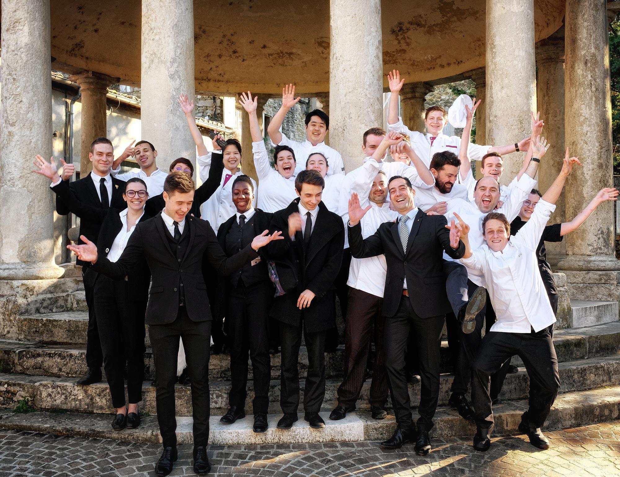 Équipe d'hôtelier et de restaurateurs en costume et veste de cuisine, les bras tendus vers le ciel pour exprimer de la joie