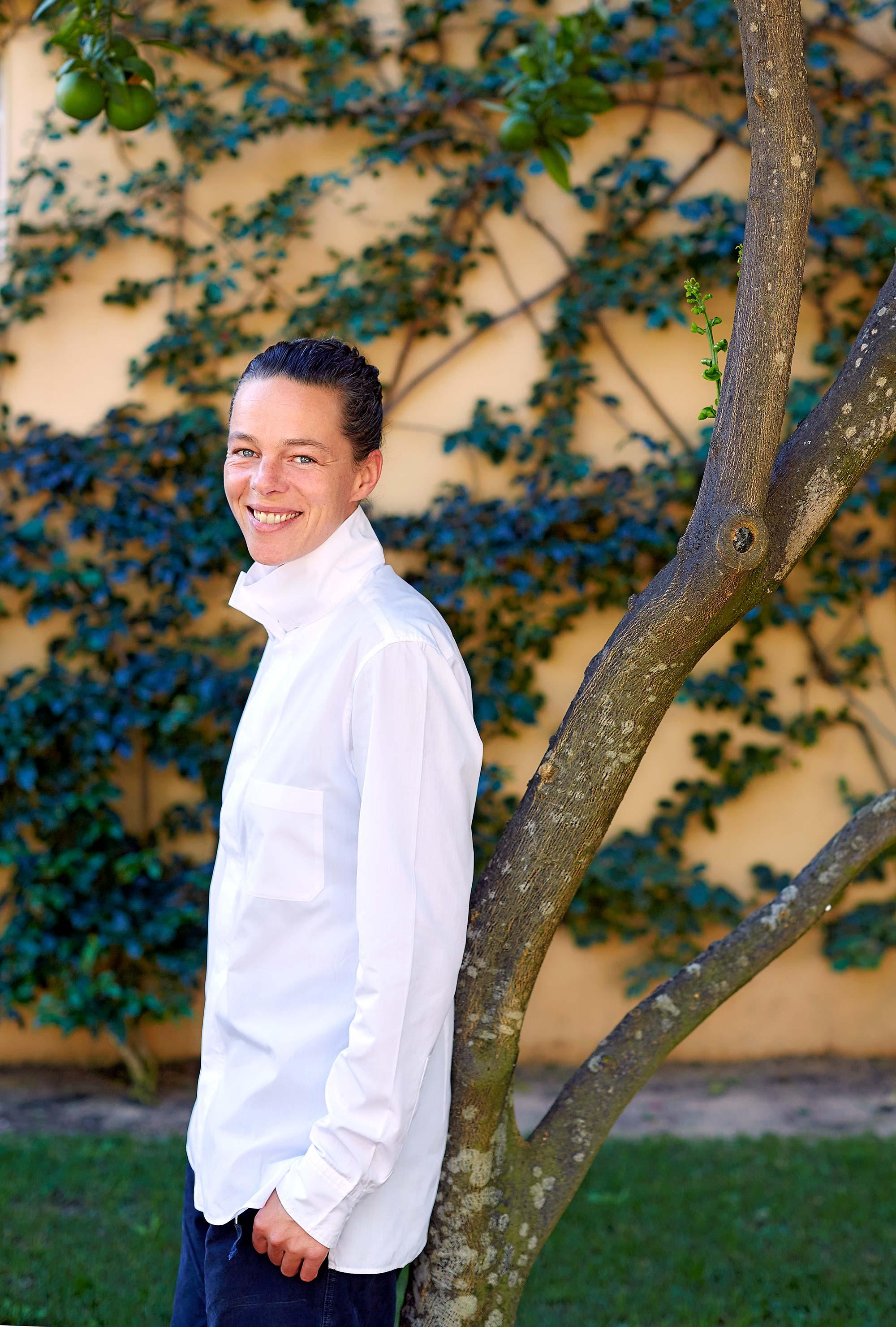Femme avec chemise blanche, adossée à un arbre dans un jardin