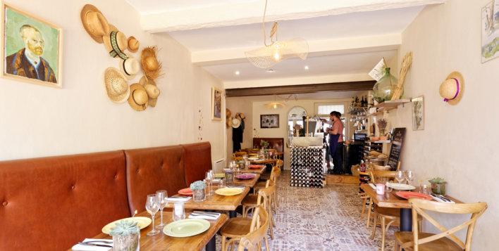 Intérieur d'une salle de bistrot typique provençale avec table et banquette bistrot, chapeau de paille accrochés au mur et toile de Vincent van Gogh