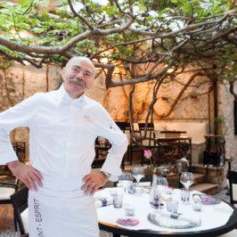 Chef en veste blanche, dans une cours intérieure ornée d'un arbre au dessus des tables dressées