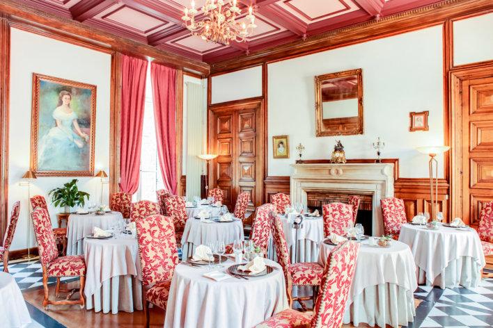 Il y a 5 tables de deux avec des chaises rouges anciens orné d'or