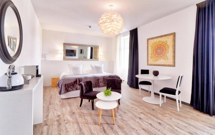 Photo de la chambre Belfry & Spa avec une petite table basse et un petit fauteuil violet situé devant le lit