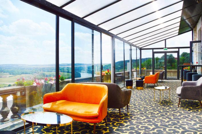Salle de restauration tapissé avec deux canapé orange et un canapé marron