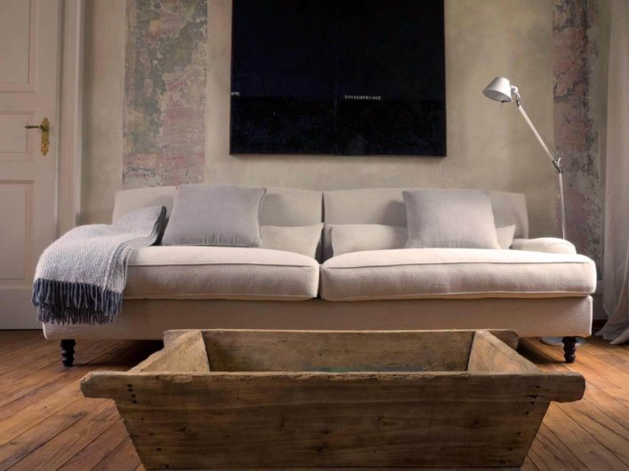 Salon canapé en tissus blanc, table basse en bois ancien, toile noire accrochée au mur