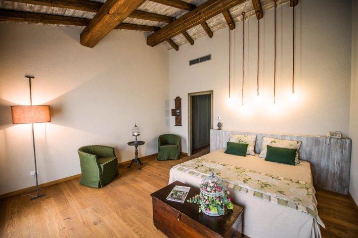 Chambre avec lit double, linge de lit blanc, poutre apparente, parquet au sol