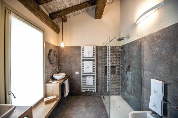 Salle d'eau avec douche à l'italienne, carrelage anthracite, poutre apparente