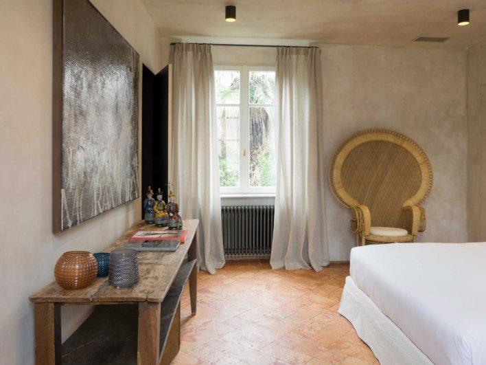 Chambre double avec fauteuil en rotin tressé, tomettes au sol et mobilier en bois anciens