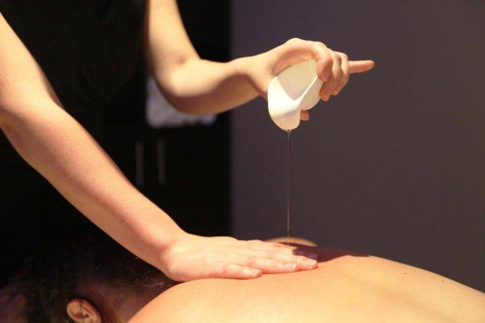 Dans une cabine de soin, une praticienne verse de l'huile de massage sur le dos d'une autre femme