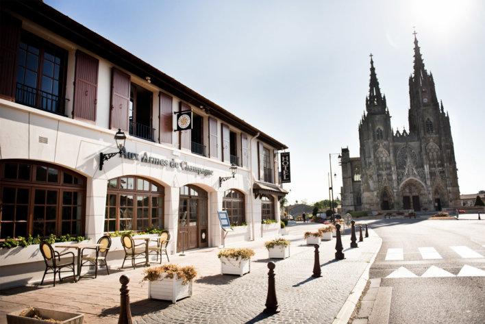Façade d'un hôtel-restaurant avec une basilique en arrière-plan