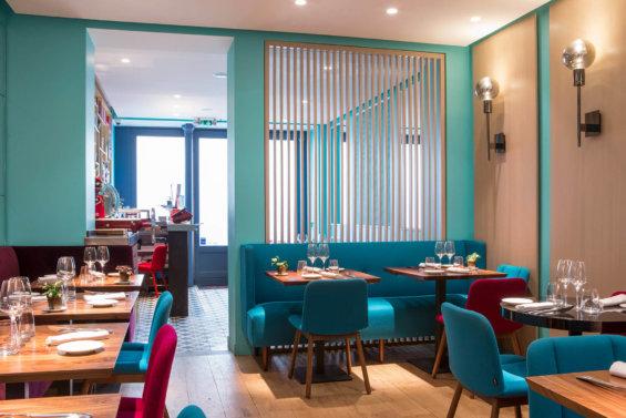 Salle de restaurant avec claustra pour séparer deux tables de l'entrée, du mobilier bleu turquoise et couleurs bois