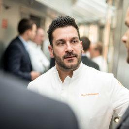 """Portrait d'un chef en veste de cuisine blanche, brodée orange """" les Collectionneurs """""""