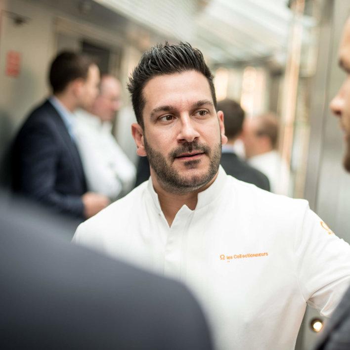 Portrait d'un chef en veste de cuisine blanche, brodée orange