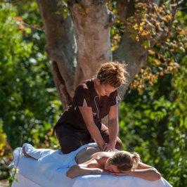 Praticienne sur le dos d'une cliente pendant un massage du dos en pleine nature
