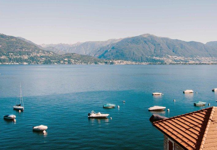 Vue sur un lac avec quelques bateau et une vue sur les montagnes en arrière-plan