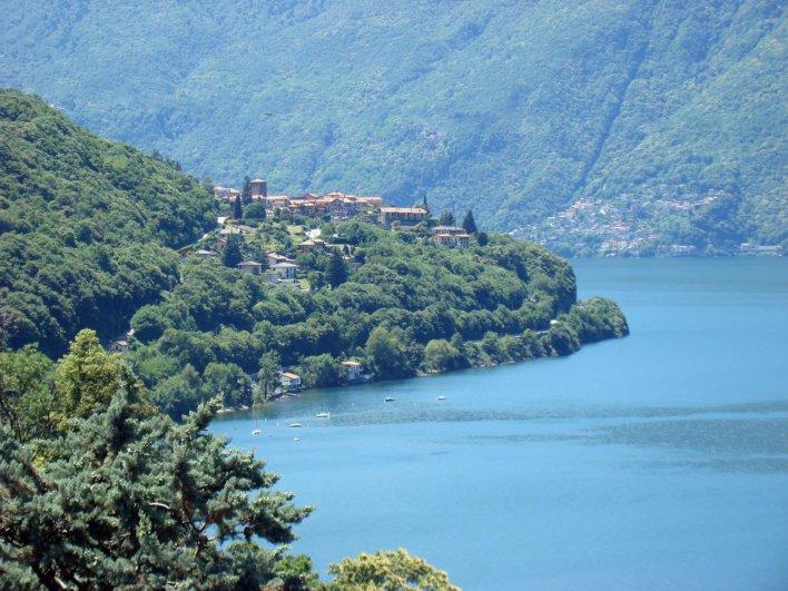 vue sur un lac avec une ville perché sur la montagne qui bord l'eau