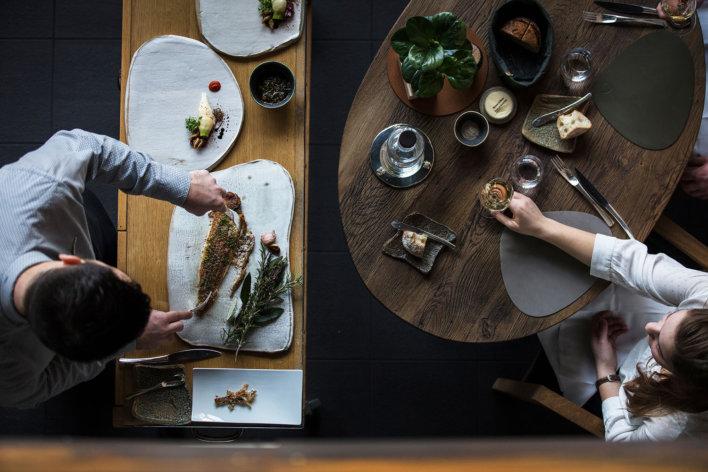 Vue aérienne sur un serveur qui découpe un poisson et une femme qui tient un verre de vin blanc attendant de se faire servir
