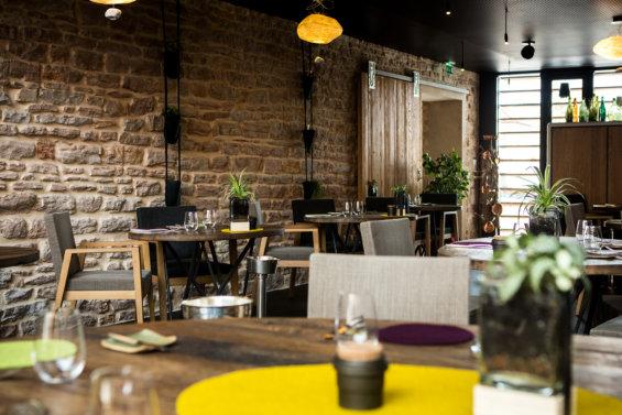 Salle de restaurant avec mur en pierre apparentes, porte coulissante dans le fond de la pièce