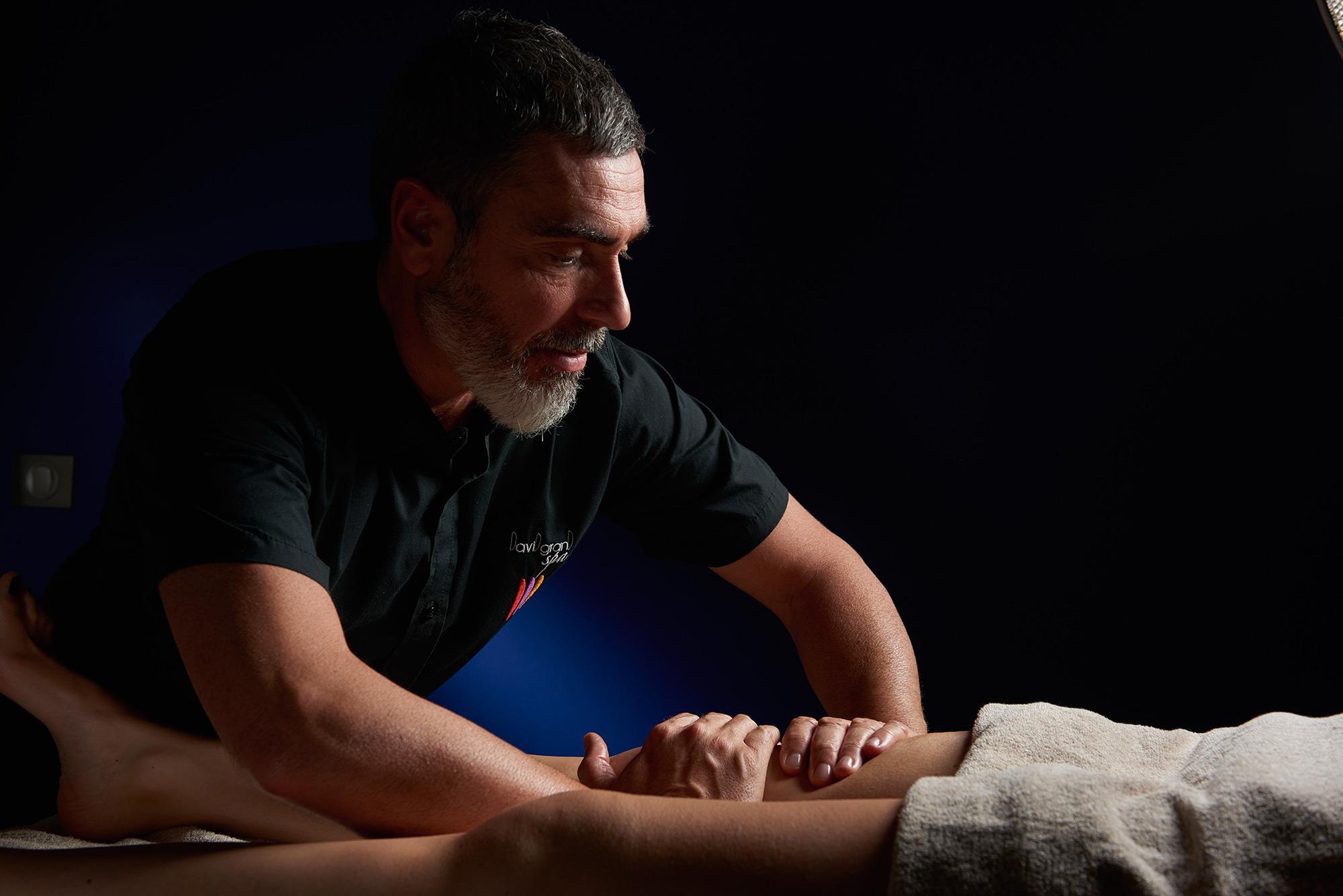 Un homme praticien réalise un massage d'une cuisse