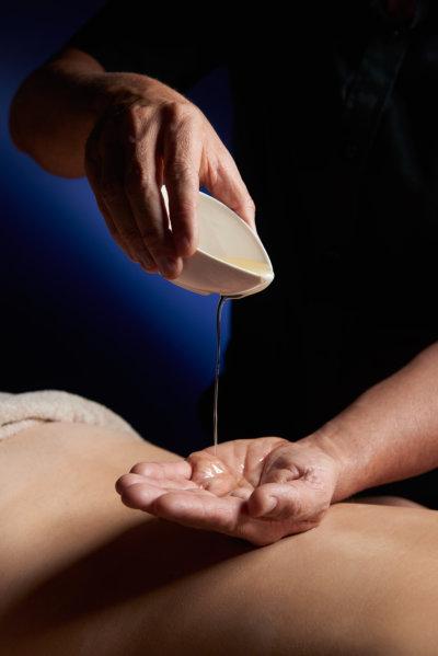 Close-up sur une main d'homme verse une huile dans son autre main pour réaliser un massage
