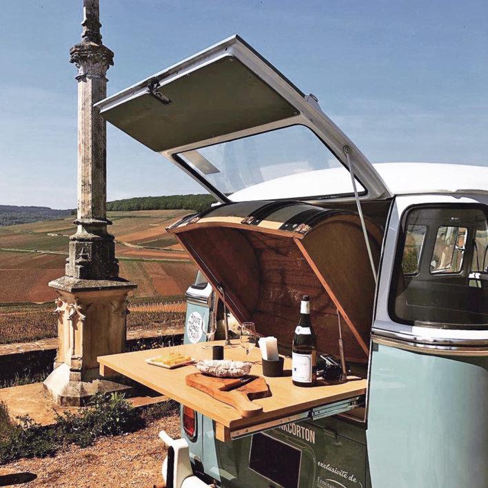 Coffre ouvert d'un combi volkswagen, sur la plage arrière est posé une planche fromages et charcuterie avec vin