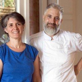 une femme en top bleu et un homme en veste de cuisine blanche l'un à côté de l'autre dans un salon