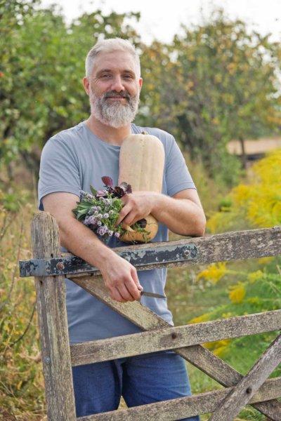Homme appuyé sur une barrière en bois, tient dans ses bras une courge et des plantes aromatiques