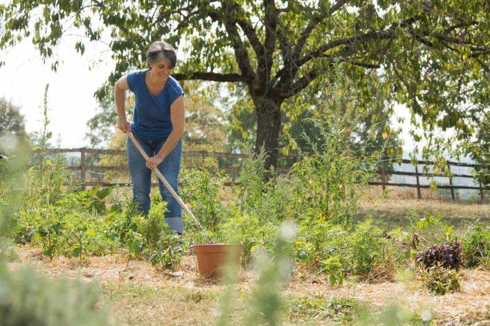 femme dans un potager en train de biner un terrain