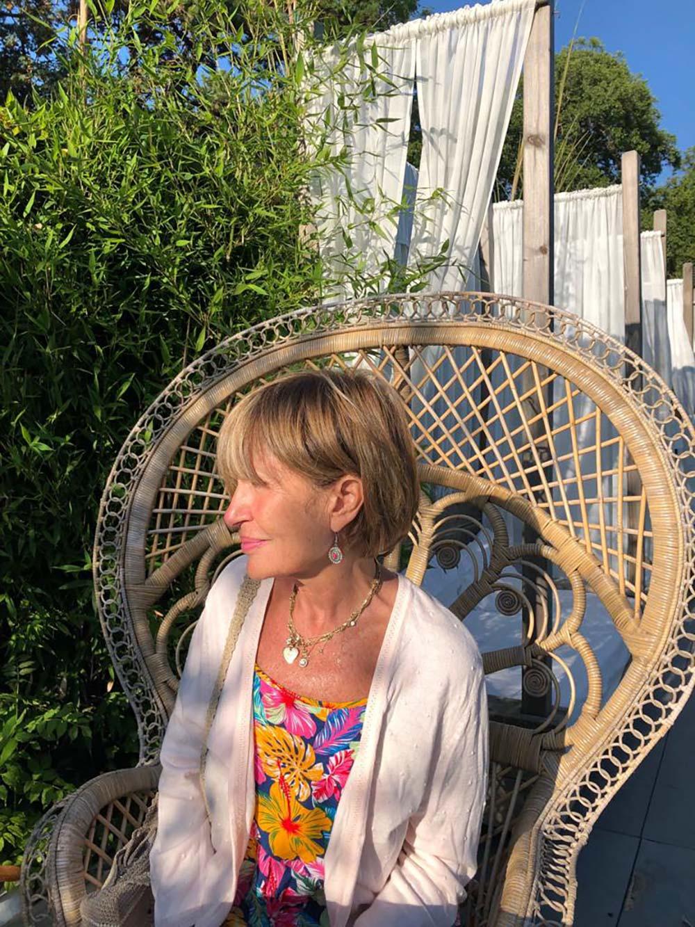 Femme assise dans un fauteuil en rotin sur une terrasse ombragée