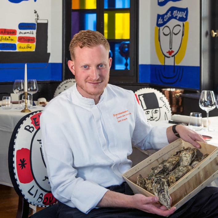 Chef en veste de cuisine blanche, assis sur une chaise, tient une bourriche d'huître