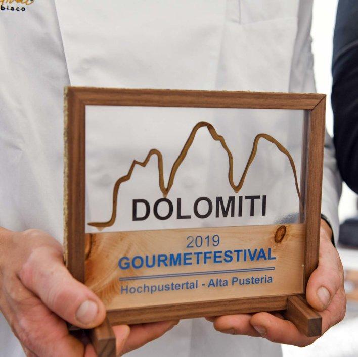 Trophée dans des mains d'hommes, gravé Dolomiti 2019 Gourmet Festival
