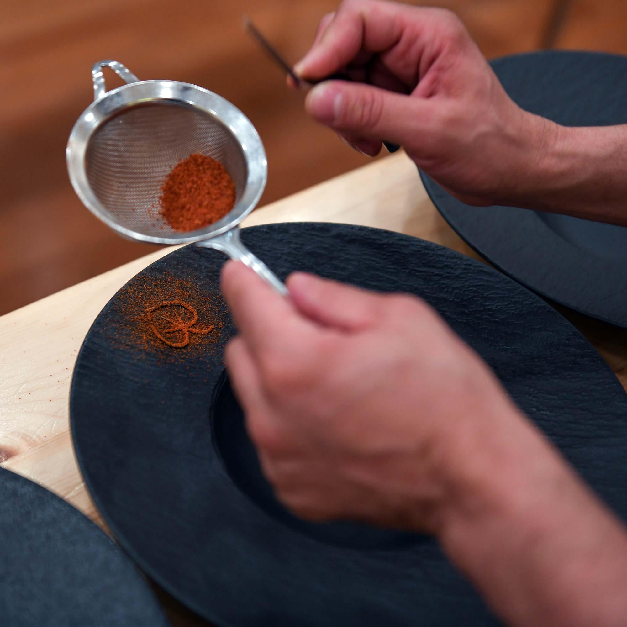 Une main dépose une épices en tamis sur une assiette