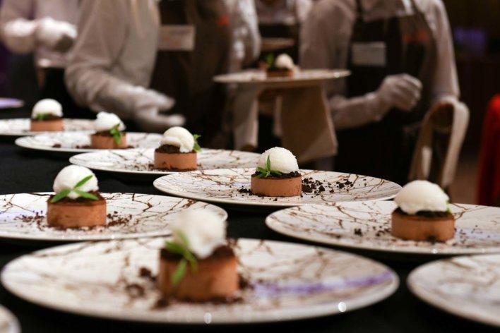 Alignement de plat gastronomiques disposés sur une table nappée noire