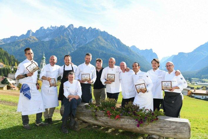 Photo collégiale de plusieurs chefs, en extérieur avec les montagnes en arrière plan