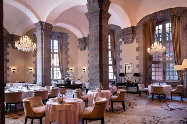 Salle de restaurant avec grande hauteur sous plafond et tout en voûte de pierres blanches
