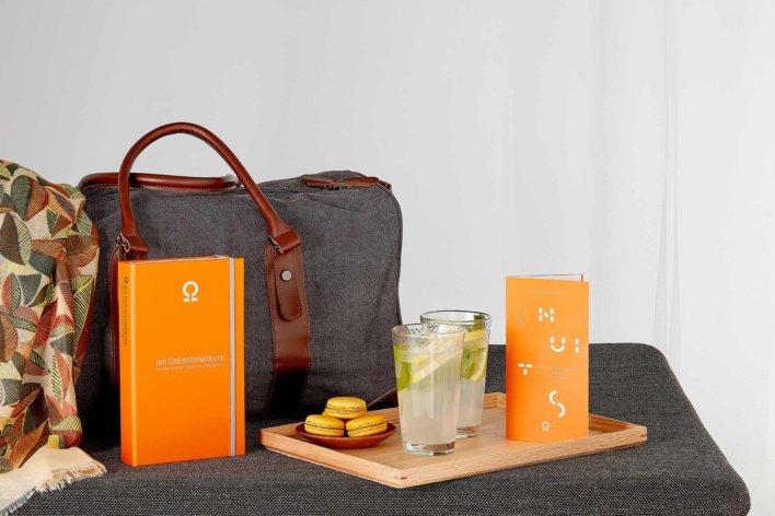 Coffret cadeau poser à coter d'une petite valise grise avec un petit plateau en bois où se trouve deux verres de mojito et une petite assiette de macarons
