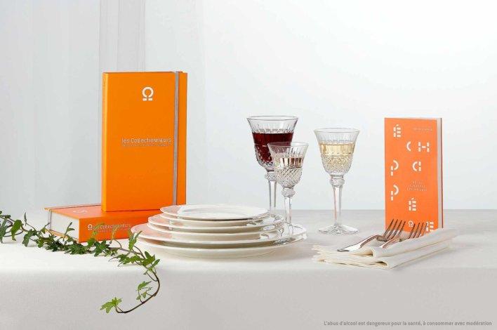Coffret sur une table nappée d'une nappe de couleur blanche avec un assortiment de couverts et d'assiettes