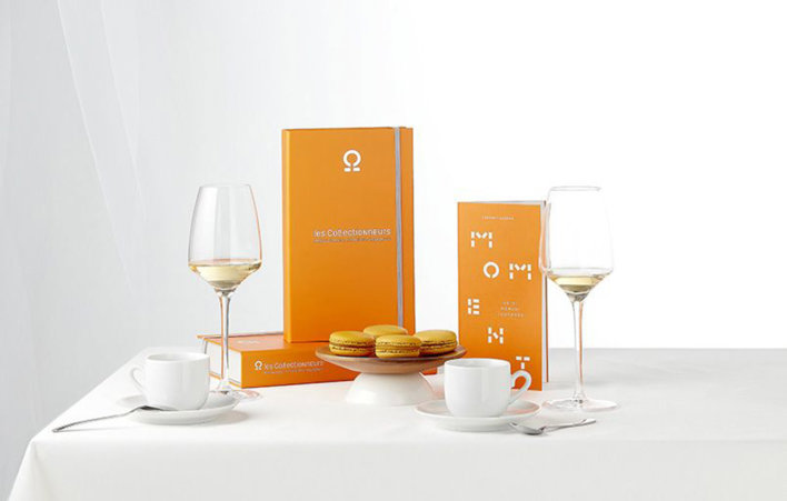 Coffret sur une table nappée d'une nappe de couleur blanche avec deux verres de vin blanc, deux petites tasses de café ainsi qu'une petite assiette de trois macarons