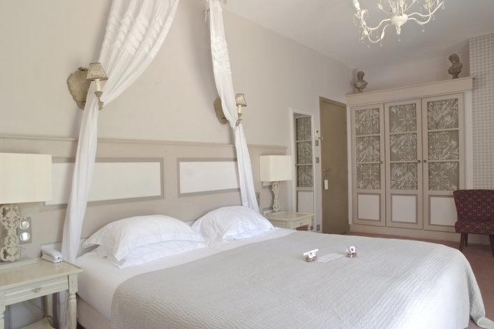 Chambre spacieuse avec une décoration de couleurs blanc et beige assez épurée avec lit double