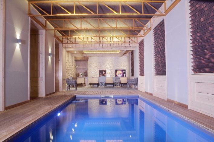 Photo du spa avec en premier plan la piscine intérieur et plus au loin un coin détente