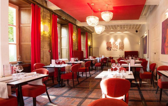 Photo de la salle du restaurant avec des sièges de couleurs rouge et des tables avec des nappes de couleurs blanche