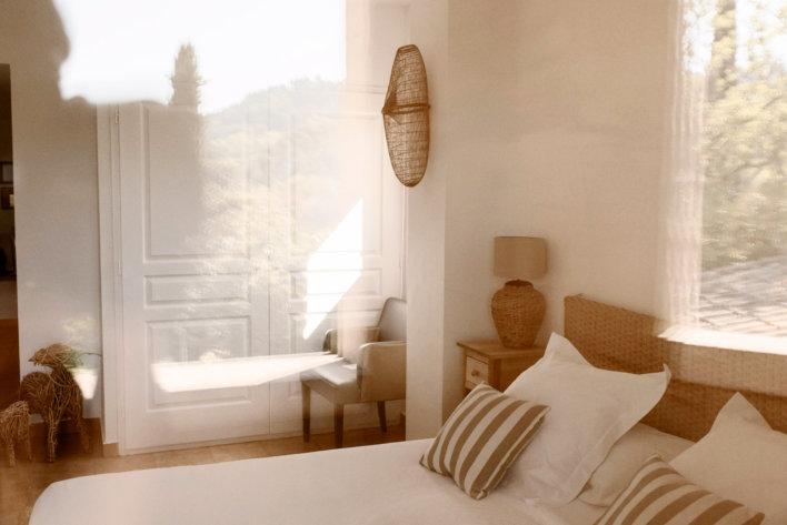 Photo prise de prêt de la chambre de l'Auberge de La Fenière avec une décoration de couleur blanc et beige assez cosy